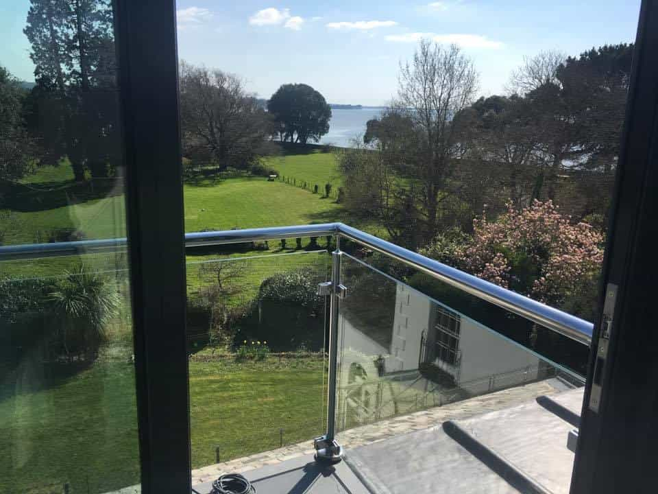 glass balcony overlooking a large garden